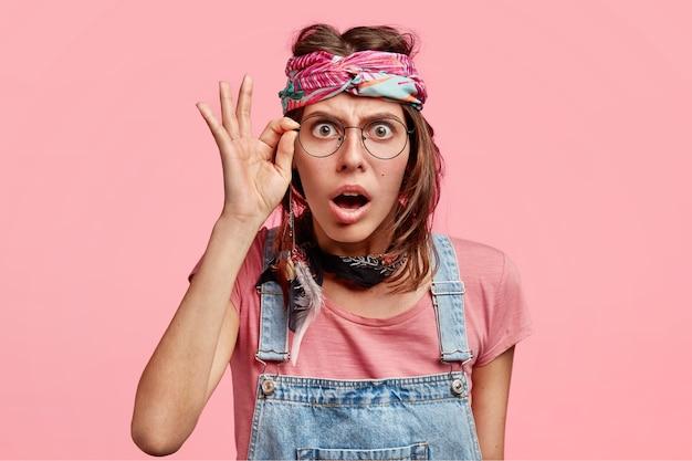 Mulher bonita hippie assustada surpresa olha através dos óculos, não consegue acreditar em más notícias, vestida de macacão e bandana, isolada sobre parede rosa
