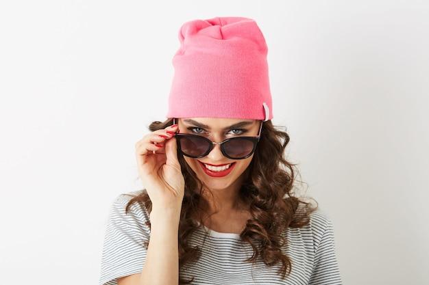 Mulher bonita hippie com chapéu rosa, óculos de sol, sorrindo, isolada, dentes brancos, lábios vermelhos, cabelo encaracolado, vestindo camiseta