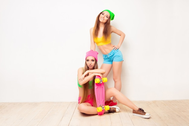 Mulher bonita hippie sentada no chão com um skate perto da irmã