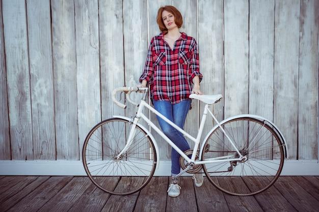 Mulher bonita hipster com uma bicicleta, em pé