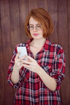 Mulher bonita hipster, concentrando-se em seu smartphone,