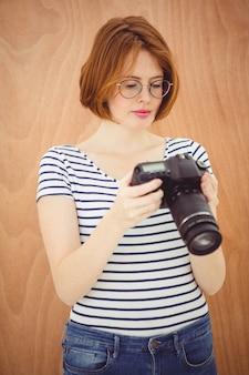 Mulher bonita hipster, olhando para a tela de uma câmera digital
