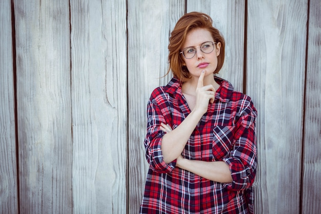 Mulher bonita hipster pensando, com o dedo no rosto,