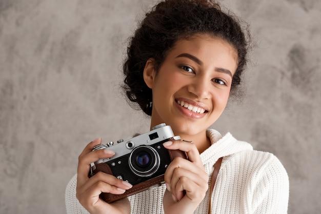 Mulher bonita hipster tirando fotos na câmera retro