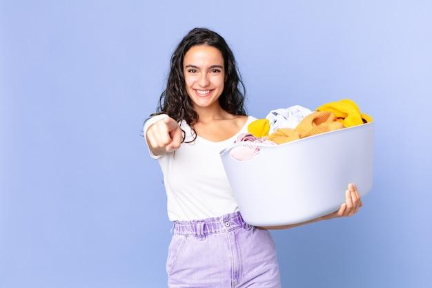 Mulher bonita hispânica apontando para a câmera escolhendo você e segurando uma cesta de roupas para lavar.
