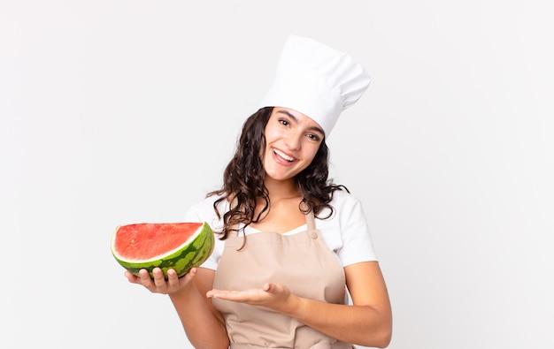 Mulher bonita hispânica chef sorrindo alegremente, se sentindo feliz, mostrando um conceito e segurando uma melancia