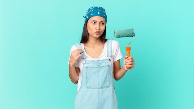 Mulher bonita hispânica com aparência arrogante, bem-sucedida, positiva e orgulhosa. conceito de pintura de casa