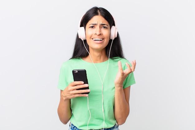 Mulher bonita hispânica com fones de ouvido e um smarphone