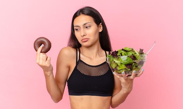 Mulher bonita hispânica com um donut e uma salada. conceito de dieta