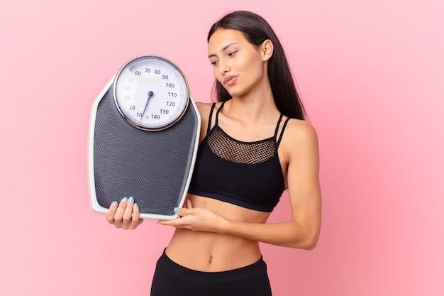 Mulher bonita hispânica com uma escala. conceito de dieta