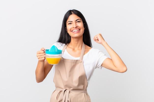 Mulher bonita hispânica do chef. suco de laranja e conceito de café da manhã