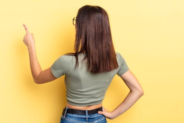 Mulher bonita hispânica em pé e apontando para um objeto no espaço da cópia, vista traseira