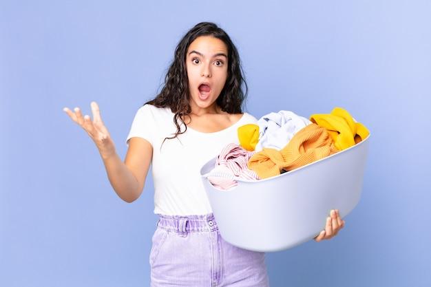 Mulher bonita hispânica espantada, chocada e atônita com uma surpresa inacreditável e segurando um cesto de roupa lavada