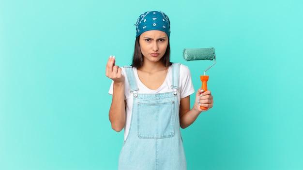 Mulher bonita hispânica fazendo capice ou gesto de dinheiro, dizendo para você pagar. conceito de pintura de casa