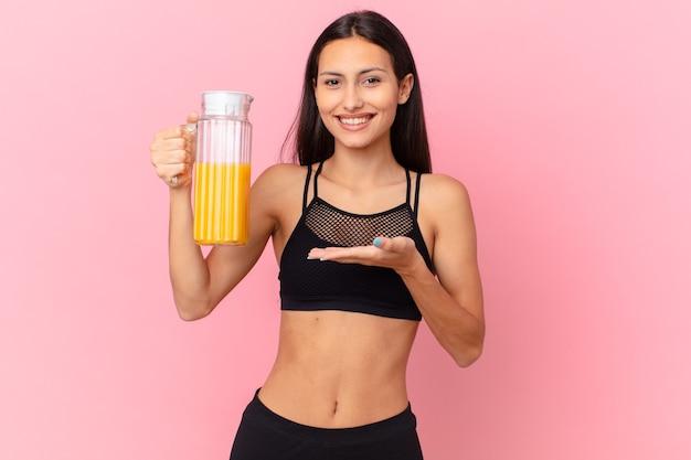 Mulher bonita hispânica fitness com um suco de laranja