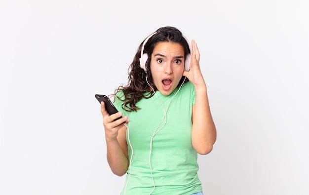 Mulher bonita hispânica gritando com as mãos para cima com fones de ouvido e um smartphone