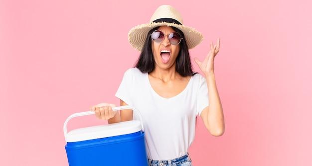 Mulher bonita hispânica gritando com as mãos para cima com uma geladeira portátil de piquenique