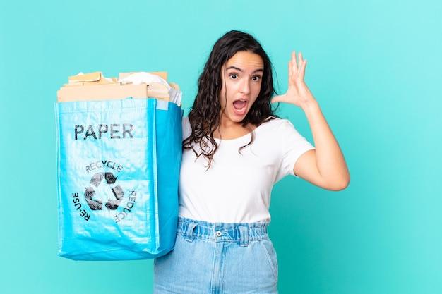 Mulher bonita hispânica gritando com as mãos para cima e segurando um saco de papel reciclado