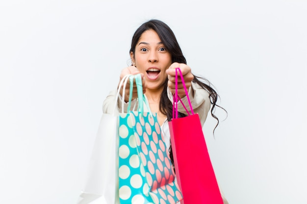 Mulher bonita hispânica jovem com sacos de compras