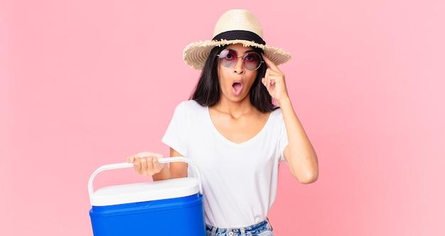 Mulher bonita hispânica parecendo surpresa, realizando um novo pensamento, ideia ou conceito com uma geladeira portátil de piquenique
