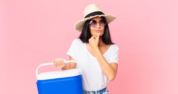 Mulher bonita hispânica pensando, se sentindo em dúvida e confusa com uma geladeira portátil de piquenique