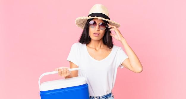 Mulher bonita hispânica se sentindo confusa e intrigada, mostrando que você é louco com uma geladeira portátil de piquenique