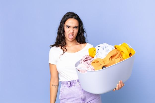 Mulher bonita hispânica se sentindo enojada e irritada, com a língua de fora e segurando uma cesta de roupas para lavar