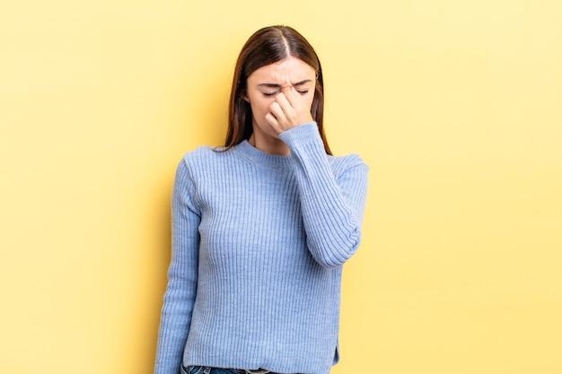 Mulher bonita hispânica se sentindo estressada, infeliz e frustrada, tocando a testa e sofrendo de enxaqueca ou forte dor de cabeça