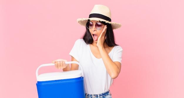 Mulher bonita hispânica se sentindo feliz, animada e surpresa com uma geladeira portátil de piquenique