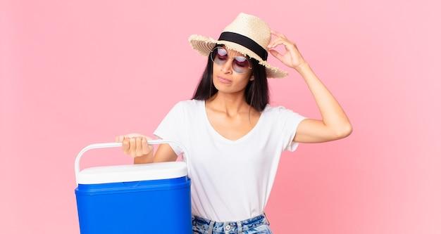 Mulher bonita hispânica se sentindo perplexa e confusa, coçando a cabeça com uma geladeira portátil de piquenique