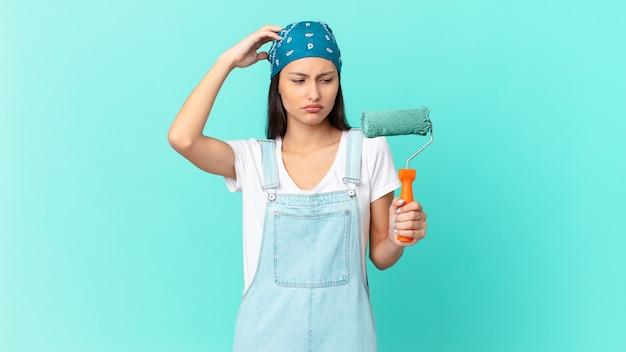 Mulher bonita hispânica se sentindo perplexa e confusa, coçando a cabeça. conceito de pintura de casa