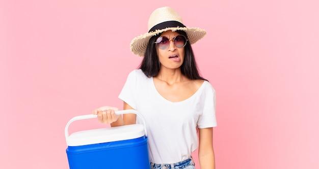 Mulher bonita hispânica se sentindo perplexa e confusa com uma geladeira portátil de piquenique