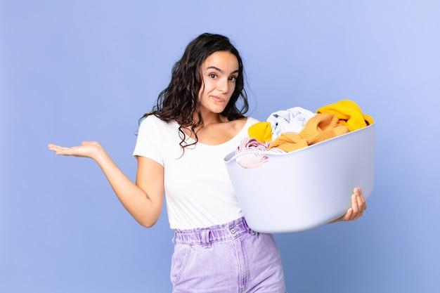 Mulher bonita hispânica se sentindo perplexa e confusa, duvidando e segurando uma cesta de roupas para lavar