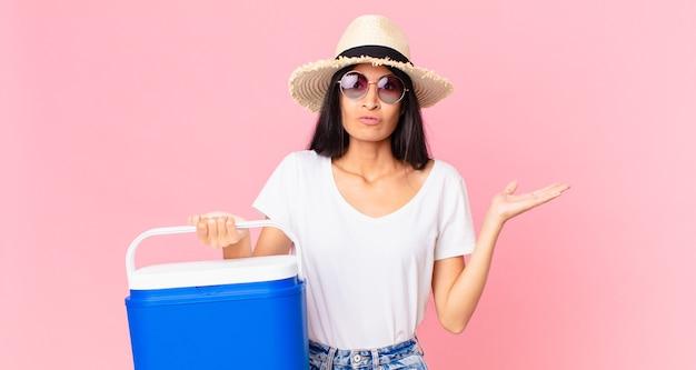 Mulher bonita hispânica se sentindo perplexa e confusa e duvidando de uma geladeira portátil de piquenique