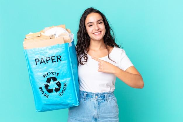 Mulher bonita hispânica sorrindo alegremente, feliz, apontando para o lado e segurando uma sacola de papel reciclado