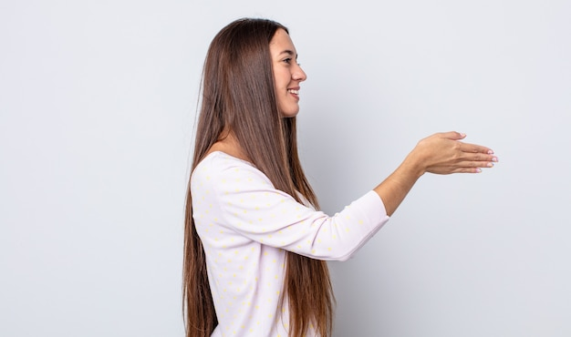 Mulher bonita hispânica sorrindo, cumprimentando você e oferecendo um aperto de mão para fechar um negócio de sucesso, o conceito de cooperação