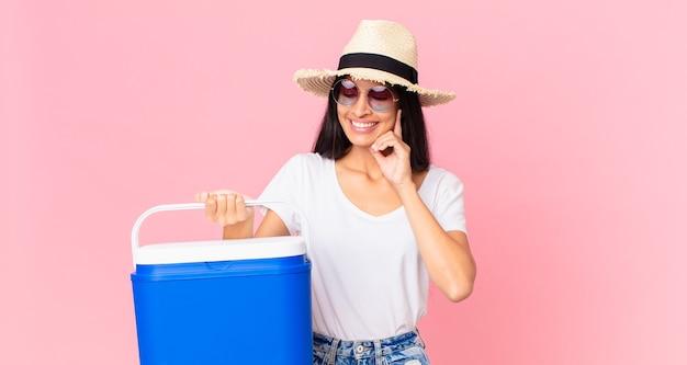 Mulher bonita hispânica sorrindo feliz e sonhando acordada ou duvidando com uma geladeira portátil de piquenique