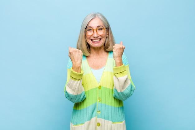 Mulher bonita idosa ou de meia-idade gritando triunfantemente, rindo e se sentindo feliz e animada enquanto celebra o sucesso