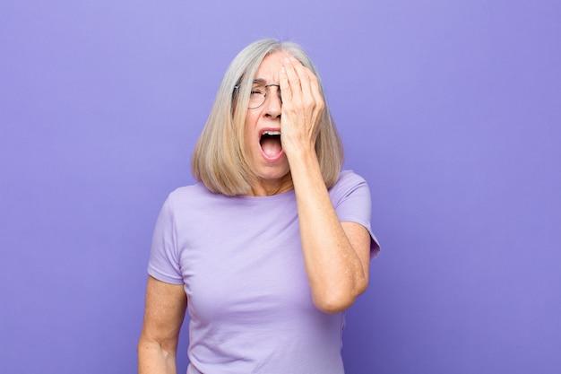 Mulher bonita idosa ou de meia-idade parecendo sonolenta, entediada e bocejando, com dor de cabeça e uma mão cobrindo metade do rosto