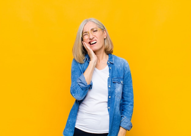 Mulher bonita idosa ou de meia-idade segurando a bochecha e sofrendo de dor de dente dolorida, sentindo-se doente, infeliz e infeliz, procurando um dentista
