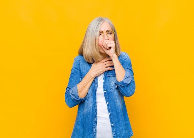 Mulher bonita, idosa ou de meia-idade, sentindo-se doente, com dor de garganta e sintomas de gripe, tosse com a boca coberta