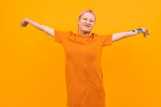 Mulher bonita incomum com cabelo rosa curto e sorrisos de tatuagem isolados em fundo laranja