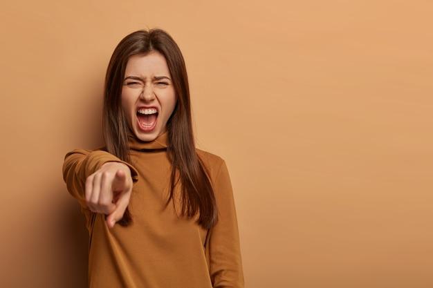 Mulher bonita indignada culpa e aponta para você com o dedo indicador, grita alto e mantém a boca aberta