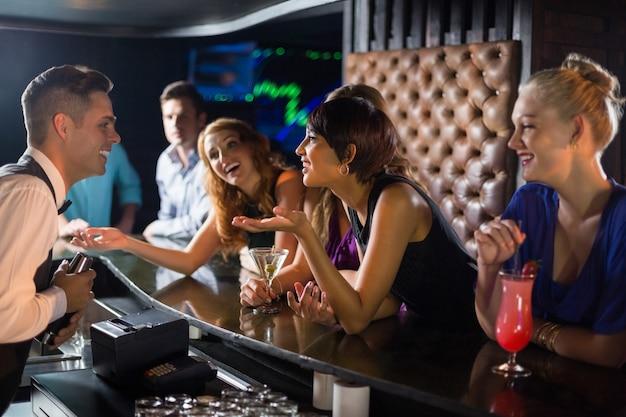 Mulher bonita, interagindo com o garçom no balcão de bar