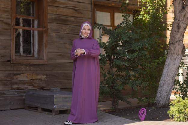 Mulher bonita islâmica em um vestido muçulmano de pé em um parque de verão rua fundo floresta outono trees.world hijab dia.