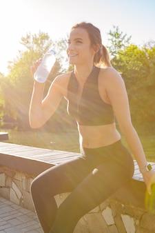 Mulher bonita jovem água potável durante a manhã jogging no parque