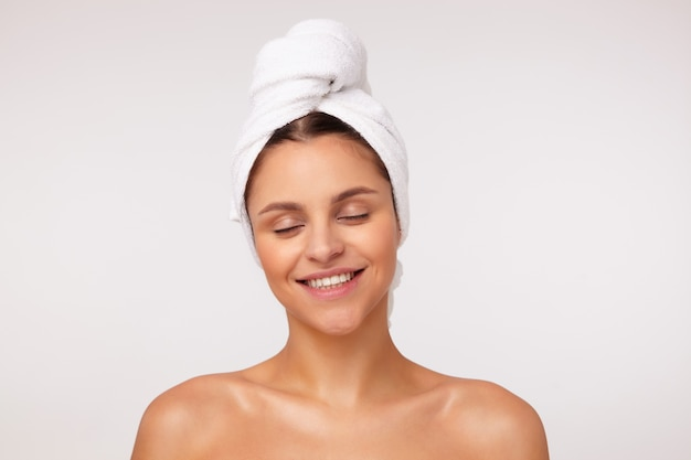 Mulher bonita, jovem, alegre, de cabelos escuros, sorrindo alegremente com os olhos fechados, estando de bom humor depois do banho, posando sobre fundo branco