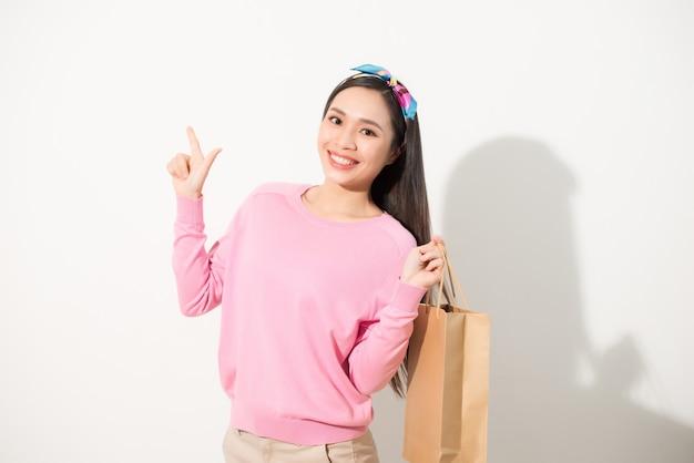 Mulher bonita jovem alegre levantando sacolas de compras, dançando e olhando para a câmera. conceito de consumismo. vista frontal isolada na parede branca.