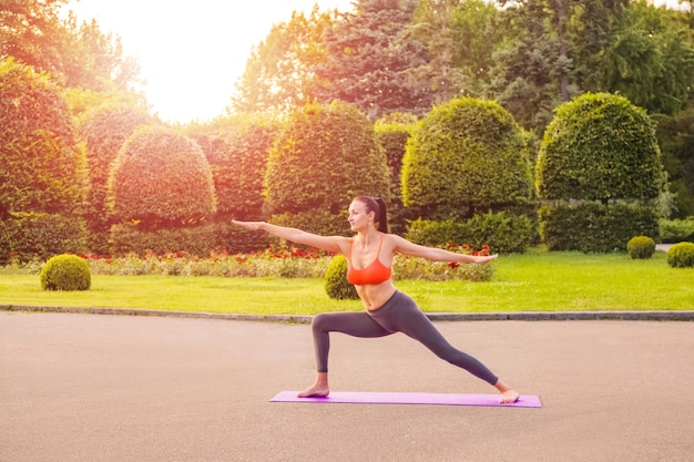 Mulher bonita jovem alegre praticando e posando de ioga no parque.