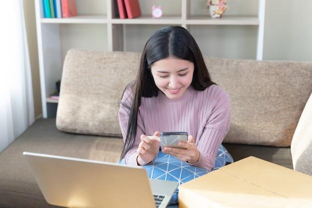 Mulher bonita jovem alegre usar smartphone na sala de estar